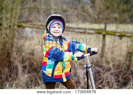 cute little preschool kid boy riding on scooter in park nature. children activities outdoor in winter, spring or autumn. funny happy child in colorful fashion clothes and with helmets. High speed