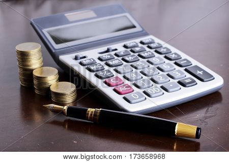 Fountain pen and calculator and coins stack on wooden table for loan money concept
