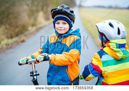 Two little kid boys, best friends riding on scooter in park nature. children activities outdoor in winter, spring or autumn. Siblings brothers in colorful fashion clothes and with helmets. High speed