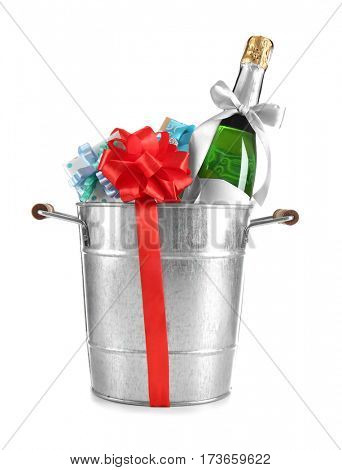 Champagne bottle and gift boxes in bucket on white background