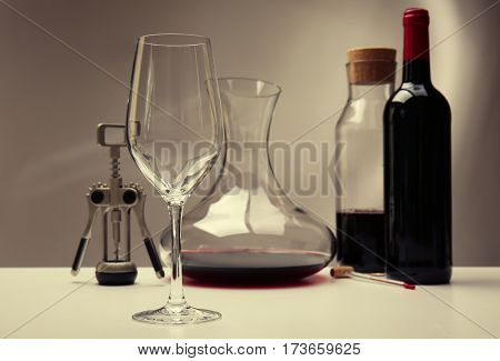 Glass and decanter with bottle on table