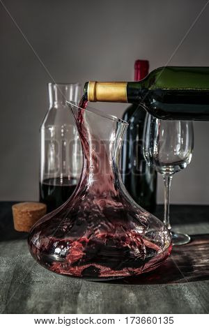 Pouring wine in carafe on table