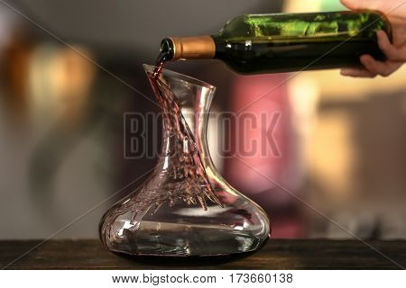 Pouring wine in carafe on blurred background
