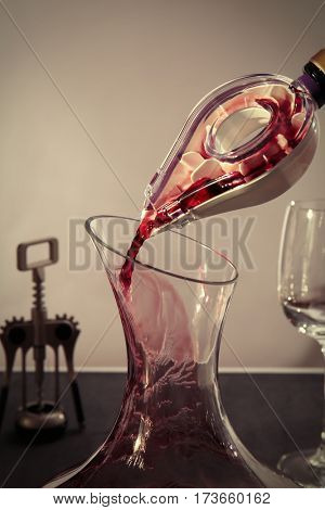Pouring wine in carafe on gray table