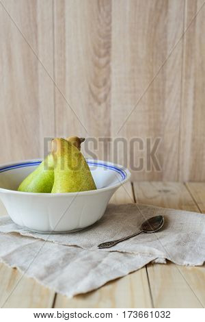 side view of two green ripe pears in bowl dish and spoon on linen doily on wooden table with copy space