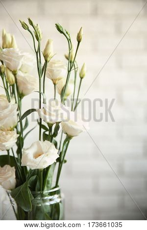 Glass vase with bouquet of beautiful flowers on color background