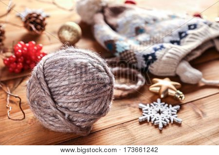 Yarn ball, knitted hat and Christmas decorations on wooden table