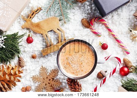 Cup of cocoa and Christmas decoration on soft fabric background