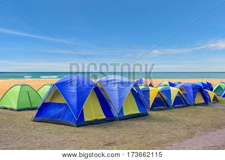 Camping and colorful tents next to a sandy beach