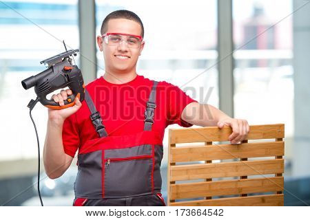 Young furniture carpenter in industrial concept