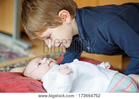 Happy little kid boy with newborn baby girl, cute sister. Siblings. Brother and baby cuddling together. Kids bonding. Family of two bonding, love.