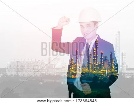 Double Exposure Of  Engineer Celebrating With Arm Raised Against Petrochemical Industrial Plant