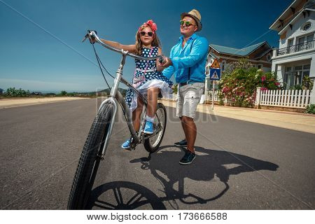 Father teaching his daughter to ride bike  in the suburb street and having fun