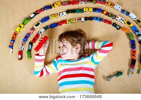 Cute little blond kid boy playing with lots of toy cars indoor. Child wearing colorful shirt. Happy preschooler having fun at home or nursery. Big collection of different vehicles. Happiness game