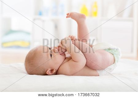 Funny little baby boy wearing a nappy playing with his legs in nursery. Cute kid sucking his feet. Child after bath or shower on bed. Infant skin care.