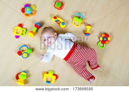 Cute adorable newborn baby playing with lots of colorful rattle toys. New born child, little girl looking surprised at the camera. Kid having fun. Family, new life, childhood, beginning concept