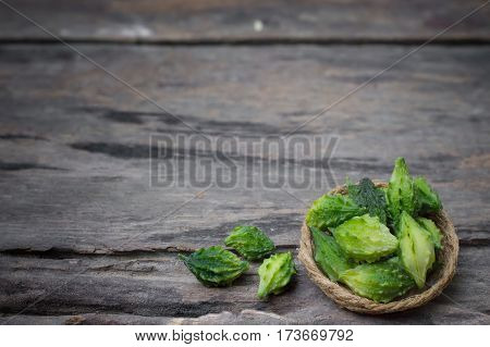 Small bitter gourd in basket on wooden table background