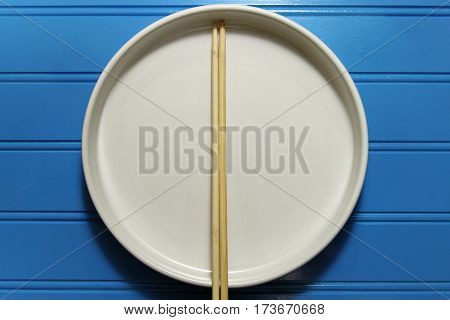 A round white plate with wooden chopsticks on blue background copy space