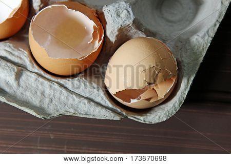 Top view of broken egg shells in a carton selective focus.