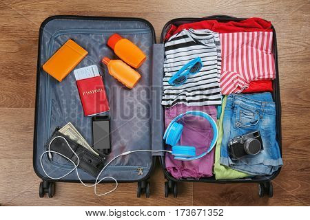 Open suitcase with travel accessories on wooden floor