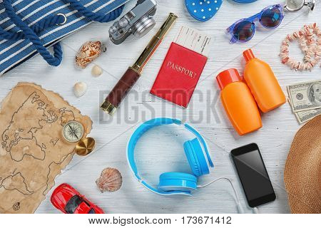 Travel accessories on light wooden background