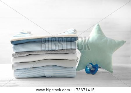 Pile of baby clothes and pacifier on wooden table