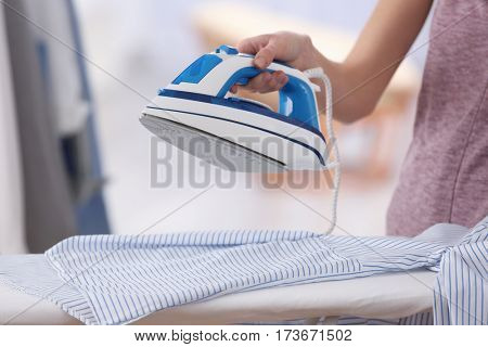 Female hand ironing clothes