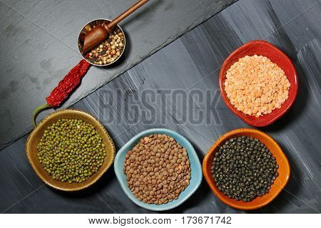 A bowl of different kings of Indian lentils and spices on grey background with copy space.