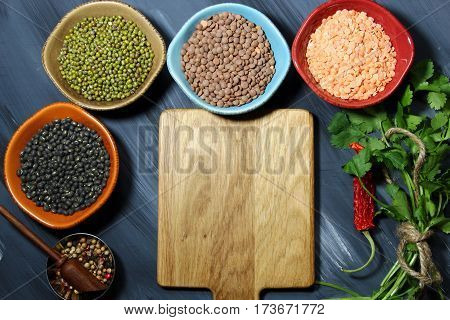 Different types of lentils in ceramic bowls (yellow brown green red french green black lentils) with copy space