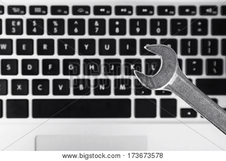 Wrench on laptop keyboard background