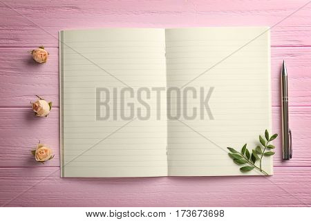 Blank opened notepad on pink wooden background