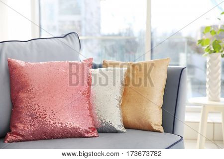 Three shiny decorative pillows on cozy sofa