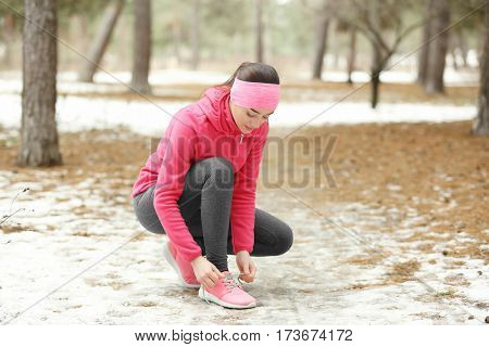 Young woman tying shoelaces in winter park