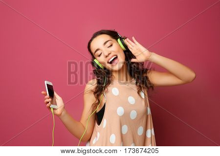 Beautiful young woman in headphones listening to music and singing on color background