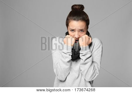 Young ill woman on grey background