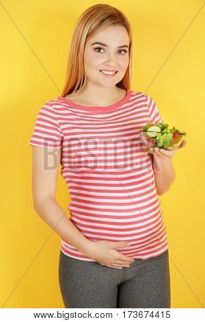 Young pregnant woman holding bowl with salad on yellow background