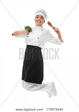 Young woman chef with broccoli and wooden spoon in hands jumping on white background
