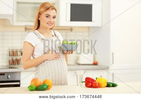 Young pregnant woman holding bowl with salad on kitchen