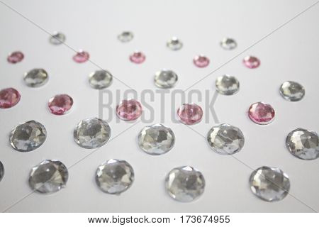 Sparkle silver and pink stones lying on white background