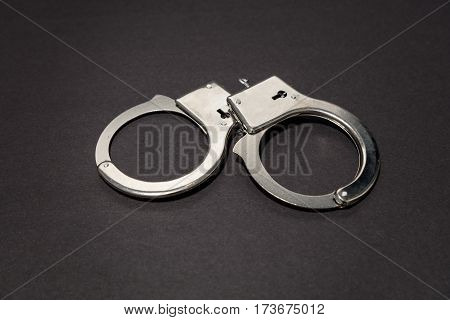 Metal handcuffs with dark background close up.