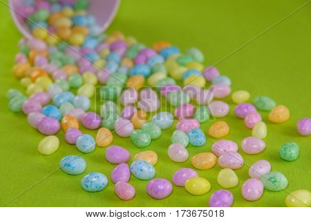 Jelly beans spilling out of a pink metal bucket on a green background