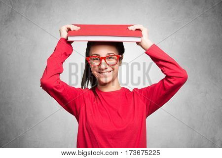 Teenager student holding a book over her head