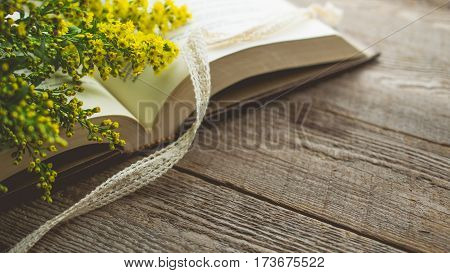 Morning relaxation and cozy with Solidago small yellow flower and white lace on the book with copy space for woman lifestyle nostalgic concept