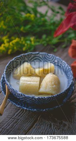 Thai banana in coconut milk with morning light on wooden background and copy space Traditional conservative secret recipe heritage