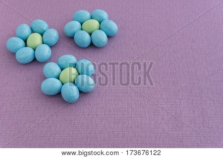 Candy coated Easter eggs in a flower pattern on a purple background