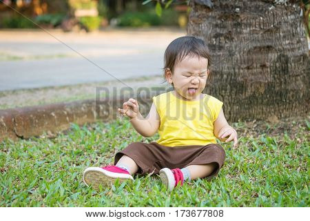 Closeup cute asian kid pull a face after he pick up hay into his mouth on grass floor in the park background