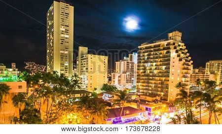 Moonlight aerial view on night traffic of Waikiki city in Oahu, Hawaii, United States. Moving people, car glowing trails in the street. City night lights of shops, shining full moon. Nightlife concept