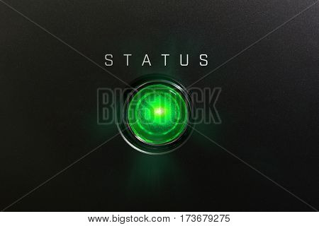 Status indicator or lamp. Green glowing warning lamp or button black panel with the words,
