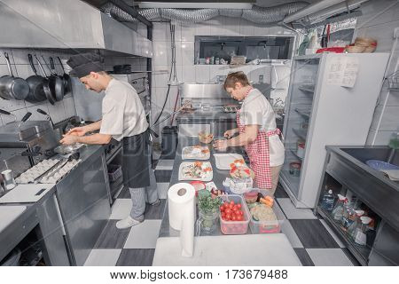 two people, chef assitant cooking food, commercial kitchen