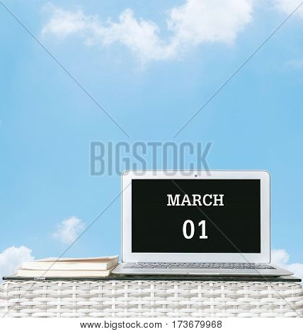 Closeup computer laptop with march 1 word on the center of screen in calendar concept on blurred wood weave table and book on blue sky with cloud textured background with copy space
